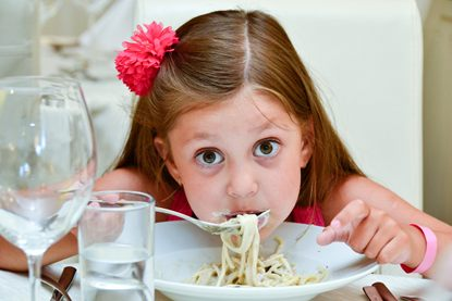 Cute girl eating pasta in Italian restaurant