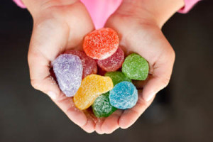 Child hands full of colorful jelly candies with sugar. Dark background
