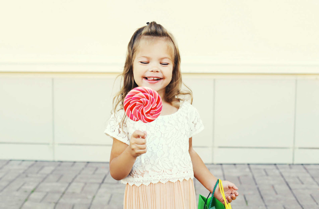 Happy smiling little girl child with sweet caramel lollipop having fun in city