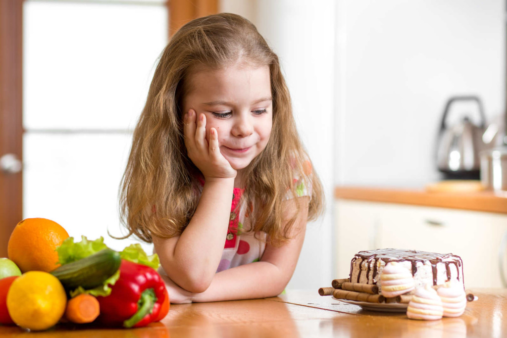 kid choosing between healthy vegetables and tasty sweets