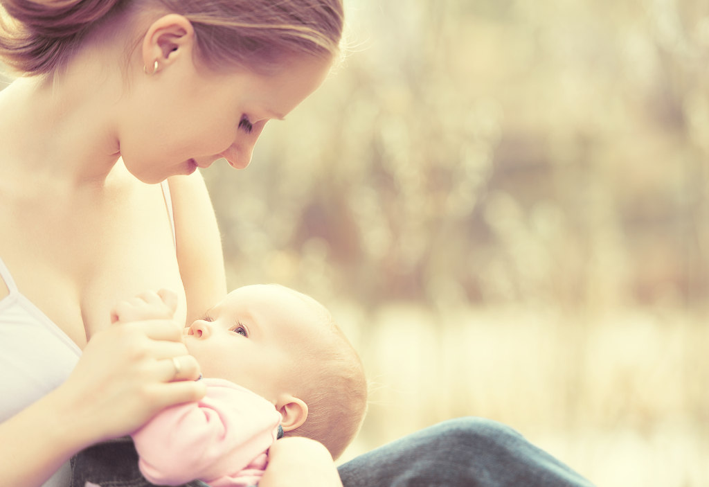 breastfeeding. mother feeding her baby in nature outdoors in the park