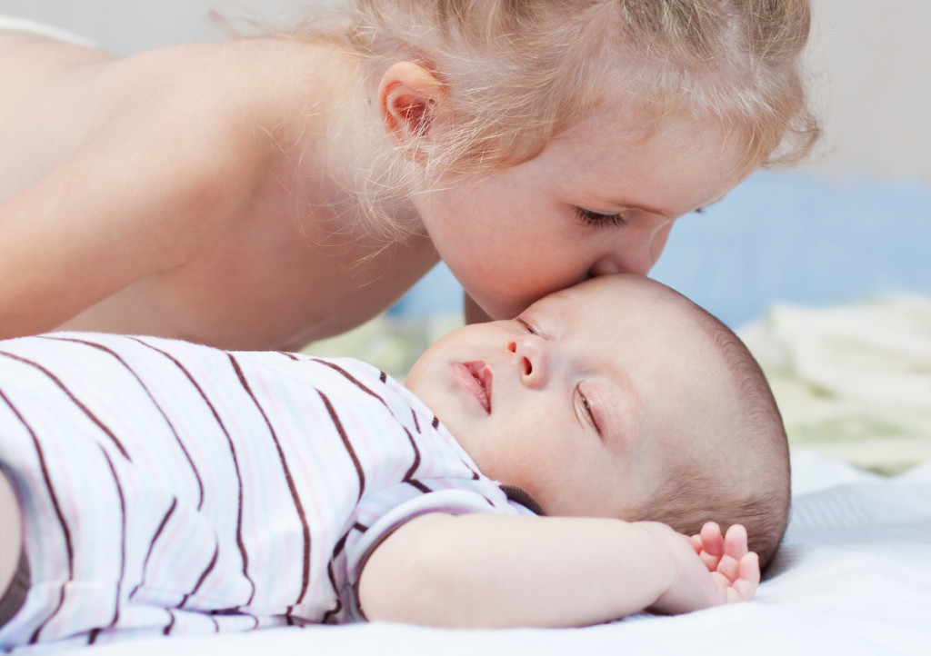 little sister kisses a sleeping newborn baby brother